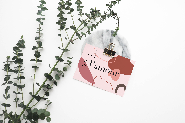 """carte postale """"l'amour"""" sur mur décoré d'eucalyptus"""